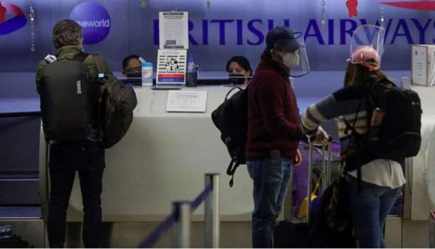 Passengers are seen at the counter of British Airways to check in for their flights to London at the