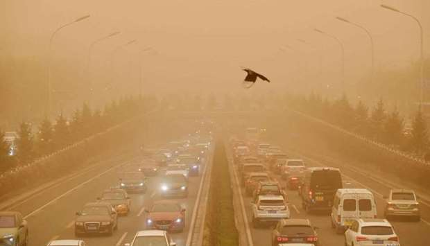 Motorists commute on a road during a sandstorm in Beijing