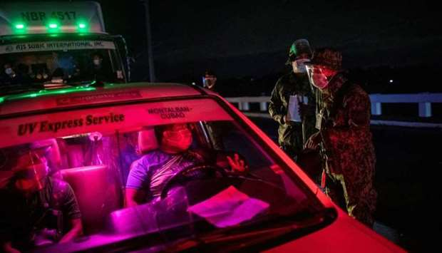 An armed policeman talks to a driver of a public transportation vehicle at a checkpoint placed to im