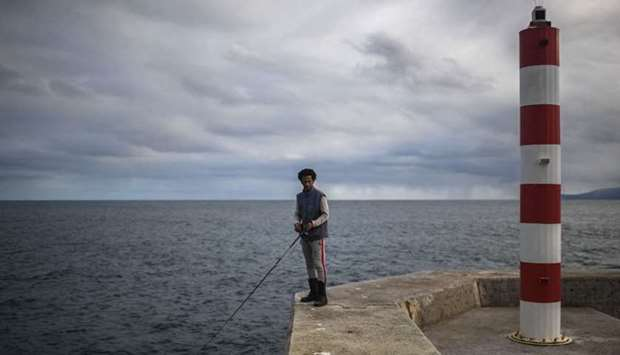 An angler holds his fishing rod on Corvo Island's pier in Azores on March 10