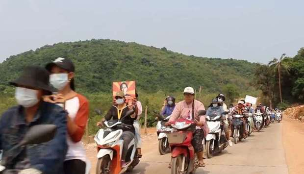 Protesters hold pictures of Aung San Suu Kyi as they ride their motorcycles in Dawei district, Myanm