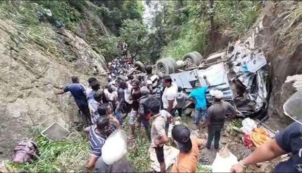 Rescue workers and locals surround the wreckage of the bus which plunged down a precipice in Passara