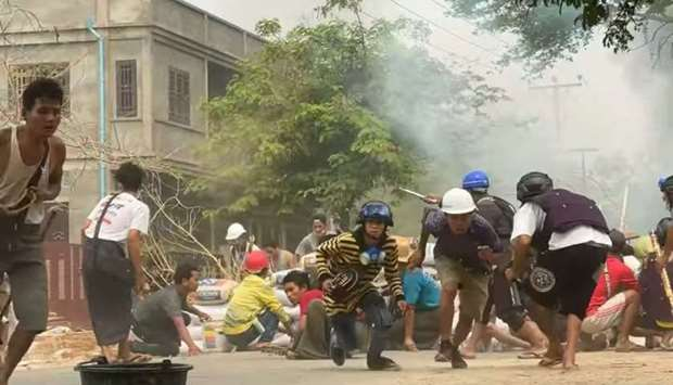 Protesters take cover during clashes with security forces in Monywa, Myanmar March 21, 2021, in this
