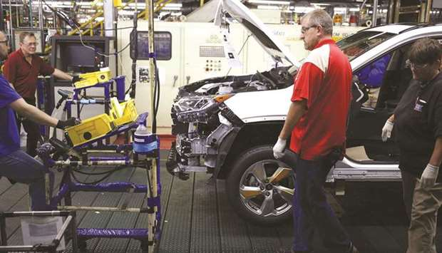 Workers install components on a RAV4 hybrid sport utility vehicle (SUV) at the Toyota Motor Corp man