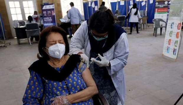 A woman receives the first dose of the coronavirus disease vaccine, as the government started vaccin