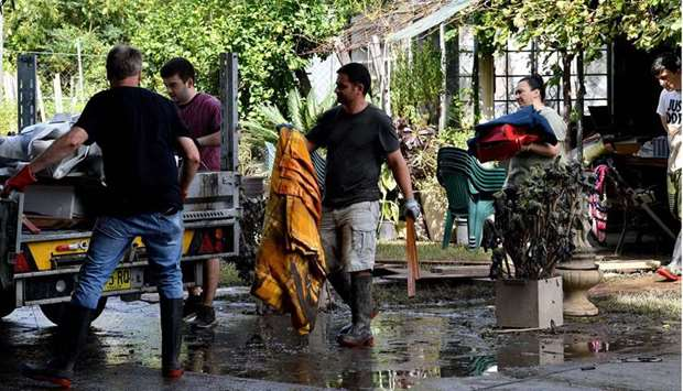 Residents clear out belongings from a home after floodwaters receded in Londonderry, a suburb outsid