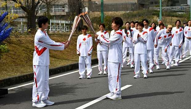 Japanese torchbearer Azusa Iwashimizu (front R), a member of the Japan women's national football tea