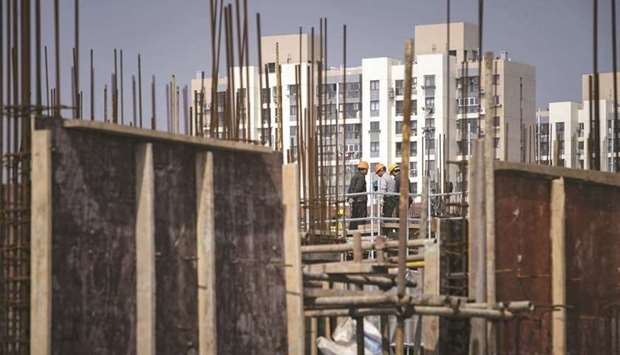 Workers stand on a scaffolding at a construction site for a residential development on the outskirts