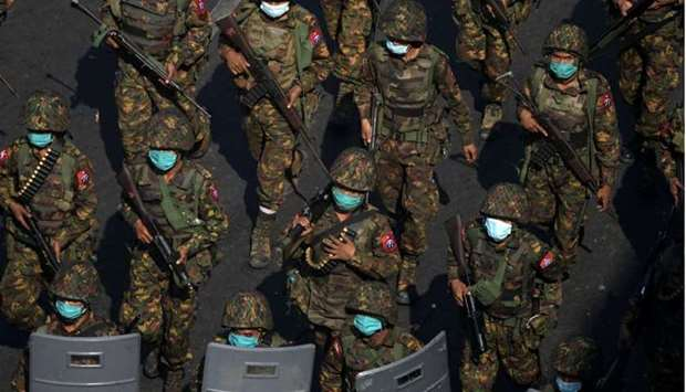 Myanmar soldiers from the 77th light infantry division walk along a street during a protest against