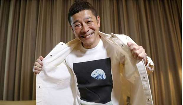 Japanese billionaire Yusaku Maezawa poses with his T-shirt bearing an image of Earth during an inter