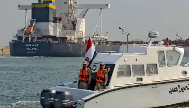 Egyptian coast guards patrol as a ship navigates the Suez Canal yesterday, a day after cargo vessel