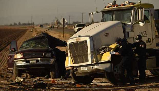 Investigators look over the scene of a crash between an SUV and a semi-truck full of gravel near Hol
