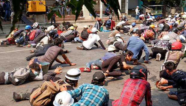 Protesters lie on the ground after police open fire to disperse an anti-coup protest in Mandalay, My