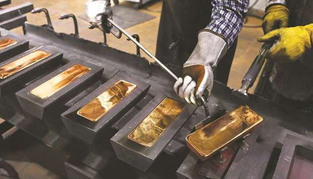 A worker uses a special tool to remove red hot gold ingots from their moulds in the foundry at the J