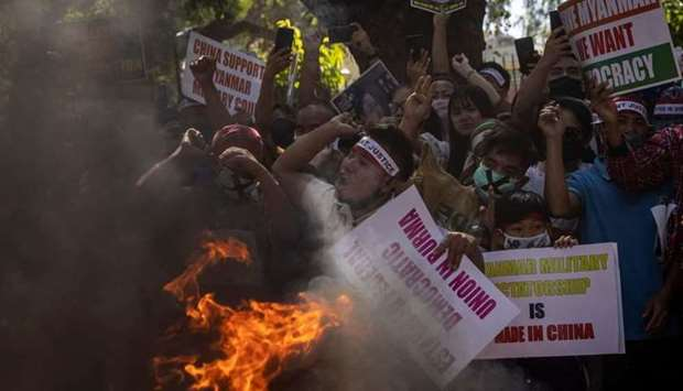 Myanmar citizens living in India shout slogans as they burn a poster of Myanmar's army chief Senior