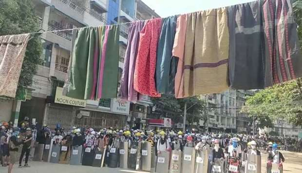 Traditional clothes hang on a rope as protesters holding shields stand in line in the background dur