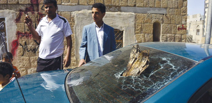 Men stand near a damaged car at the scene of a bomb blast in Sanaa yesterday.