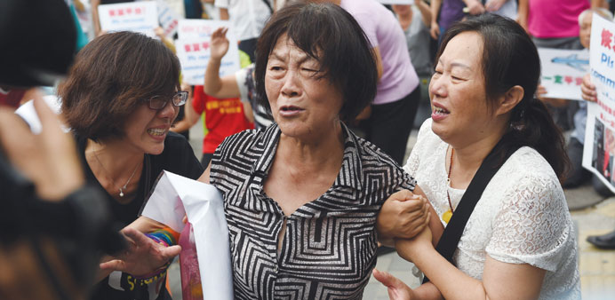Relatives of passengers on  MH370 crying outside the Malaysian embassy in Beijing yesterday.