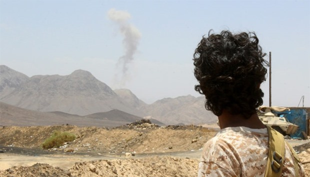 A Yemeni fighter looks at smoke rising in the distance in the Sirwah area