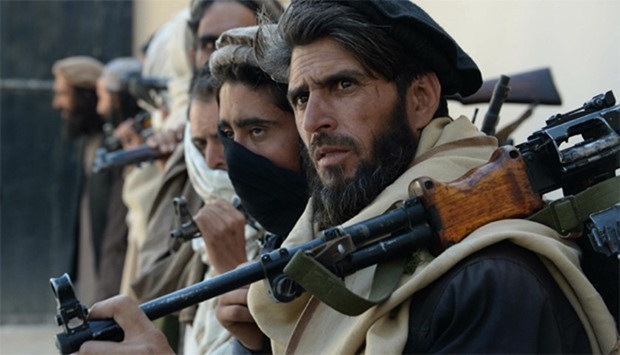 Afghan Taliban fighters carrying their weapons