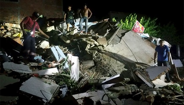 People stand next to the debris of a building after a 7.8 magnitude earthquake struck off in Ecuador