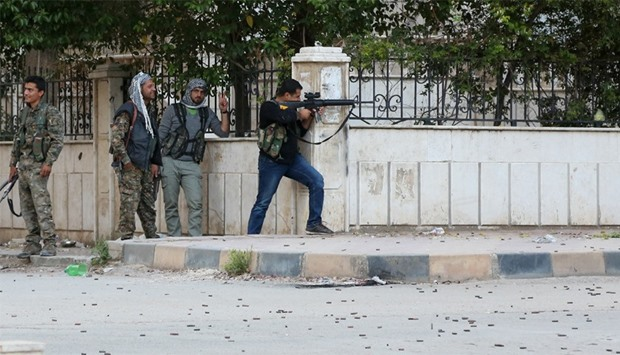 Kurdish fighters take position during clashes with Syrian pro-government in the northwestern Syrian
