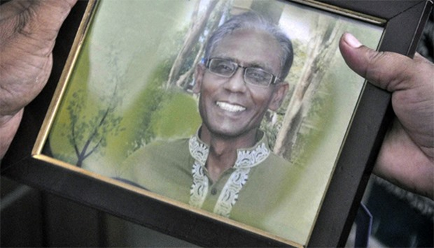A man holds a portrait of Bangladeshi professor Rezaul Karim Siddique