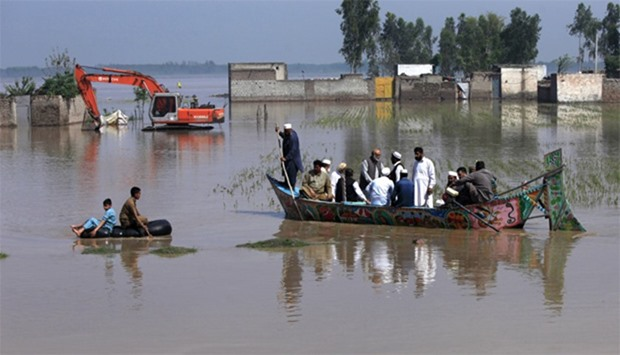 Residents use boats and inner tubes to float around in floodwater after heavy rain in Peshawar