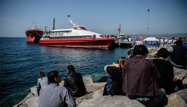 People gather on the beach as migrants arrive aboard a small Turkish ferry in the port of Dikili dis