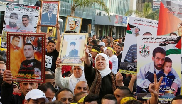 Palestinians hold pictures of relatives held in Israeli jails during a rally marking Palestinian Pri