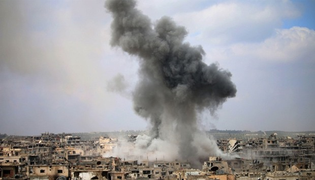 Smoke billows following a reported air strike on a rebel-held area in the southern Syrian city