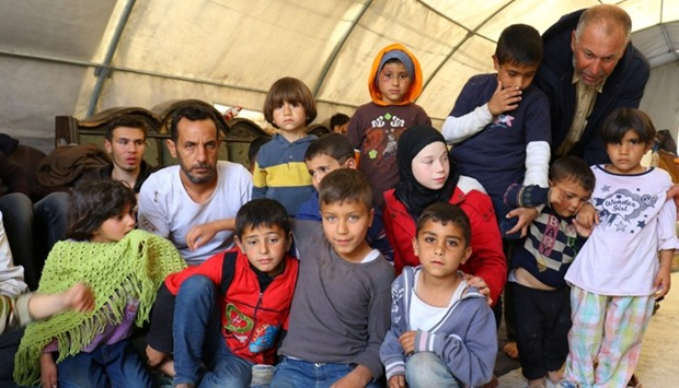 Chidren, who were in the bus convoy that was hit by a bomb blast outside Aleppo on Saturday, gather
