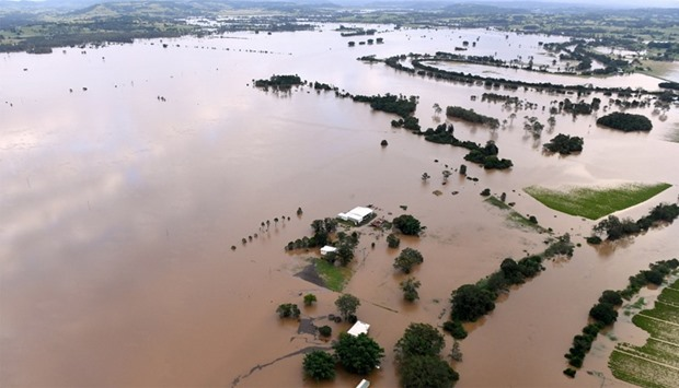 Farmland and buildings can be seen surrounded by floodwaters