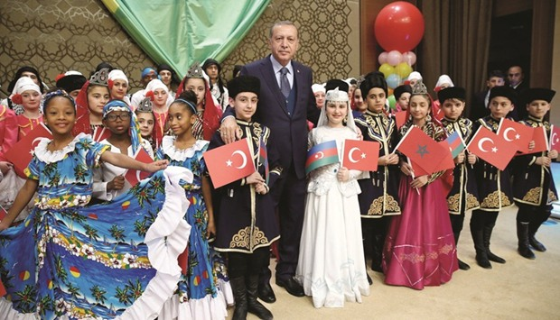 Erdogan poses yesterday with visiting children at the Presidential Palace in Ankara.