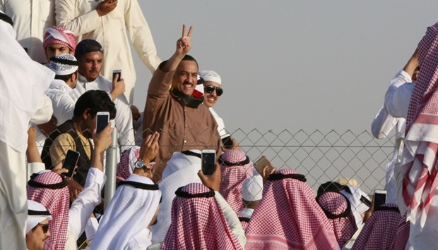 Supporters of Kuwaiti opposition leader Mussallam al-Barrak (C) celebrate his release from jail on A