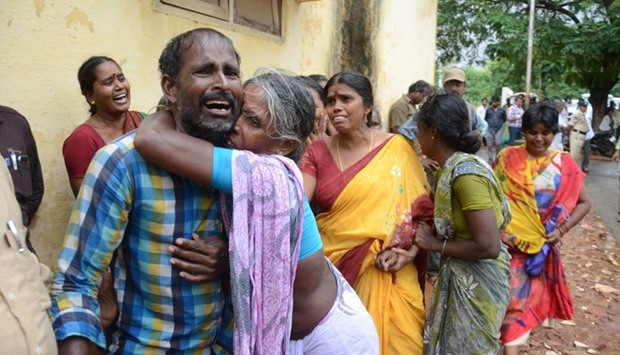 Indian relatives comfort each other as they gather at a hospital in Yerpedu near Tirupati
