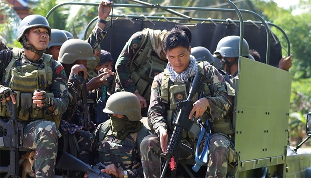 Philippine soldiers ride in the back of a military truck