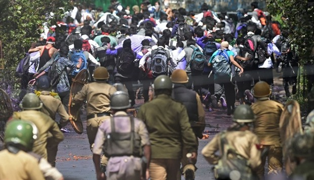 Indian government forces  chase Kashmiri students during clashes