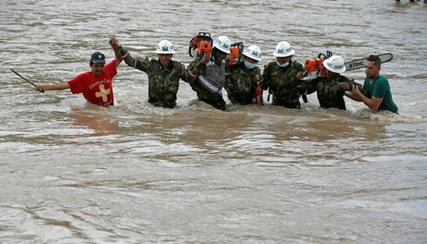 Rescuers walk in the river with chainsaws after flooding and mudslides caused by heavy rains in Moco