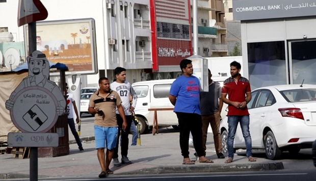 People wait at an 'open air' bus stop in Doha's Najma area.