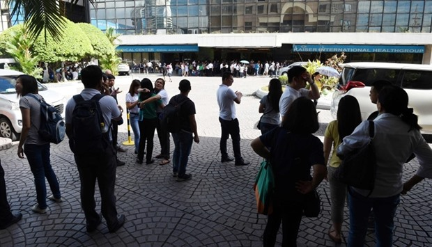Office workers stand on the grounds of an office building in the financial district of Makati in Man