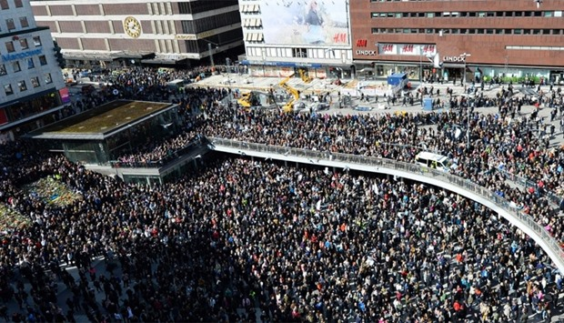 People attend a memorial ceremony at Sergels Torg plaza in Stockholm
