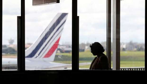 A passenger walks as Air France planes are parked on the tarmac at Orly Airport near Paris