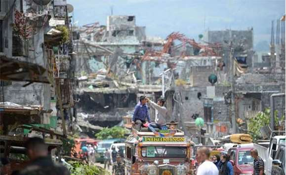Residents on top of their jeepney take photos of destroyed buildings in Marawi City on Sunday