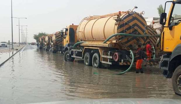 Tankers engaged in removing rainwater from a street.