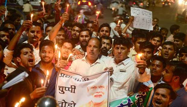 Indian Congress workers participate in a candle light procession as they shout slogans against India