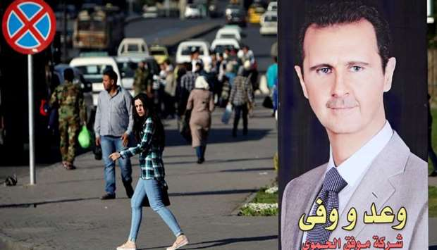 A woman walks near a picture of Syrian President Bashar al Assad in Damascus.