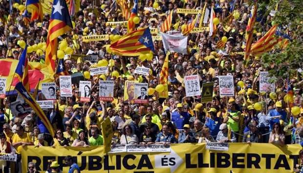 """People march behind a banner reading """"Republic is freedom"""" and wave Catalan pro-independence 'estela"""