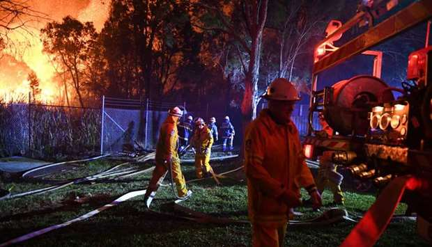 Firefighters fight flames close to homes in Corryton Court, Wattle Grove in Sydney yesterday.
