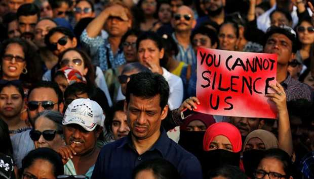 A woman holds a placard as she participates in a protest against the rape of an eight-year-old girl
